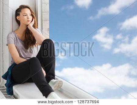 people, emotion and teens concept - sad unhappy pretty teenage girl sitting on windowsill and looking through window over blue sky and clouds background