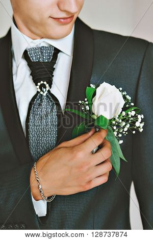 men's blue suit, red tie, white shirt. The groom adjusts his boutonniere of roses