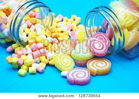 Colorful spiral jelly and colorful marshmallows with glass jars on blue-white background. Focus on jelly and marshmallows on floor.   Space for texts.