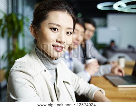 portrait of a young asian business woman looking at camera during meeting in office.