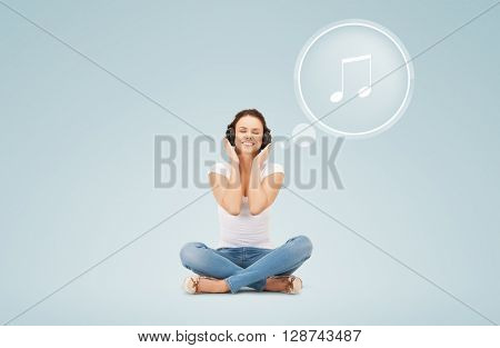 technology, music and happiness concept - smiling young woman or teen girl in headphones over blue background and musical note icon