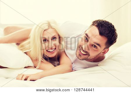 people, family, bedtime and happiness concept - happy couple lying in bed at home