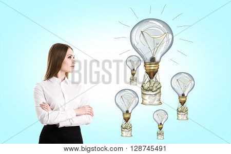 Success concept with businesswoman looking at lightbulb airballoons with money nags