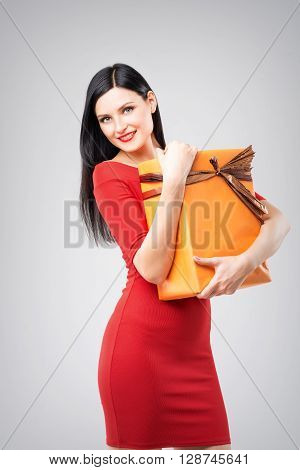 Attractive caucasian woman in red dress holding orange present box on grey background