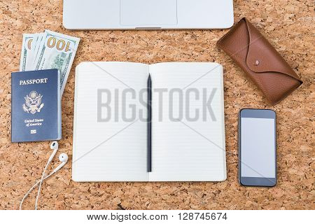 Top view of cork table with open notepad and pencil american passport and money blank smartphone and brown eyeglass case. Traveling concept. Mock up