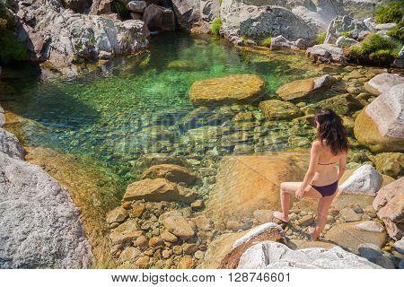 brunette woman purple bikini barefoot standing on rock looking green water pond of river lake or lagoon in summer Gredos Avila Spain Europe