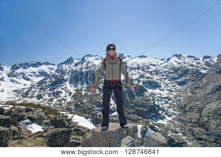 brunette sport active woman with green jacket black trousers and sunglasses posing looking on top rock with blue sky and snow peak mountains in Gredos Avila Spain Europe