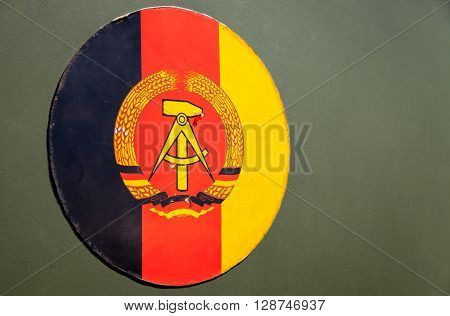 GRIMMEN/ GERMANY - MAY 1: German Democratic Republic emblem on green background on may 5 2016 in Grimmen / Germany.