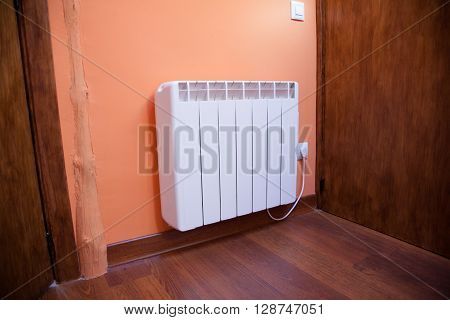white electric radiator heater plugged in orange wall wooden vinyl floor and brown wood door