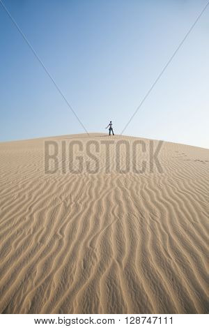 happy woman with blue jeans posing on top of sand dune looking in Maspalomas desert Gran Canaria Canary Islands Spain Europe