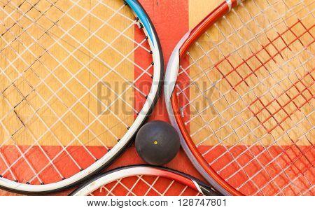 squash ball among squash rackets on the court