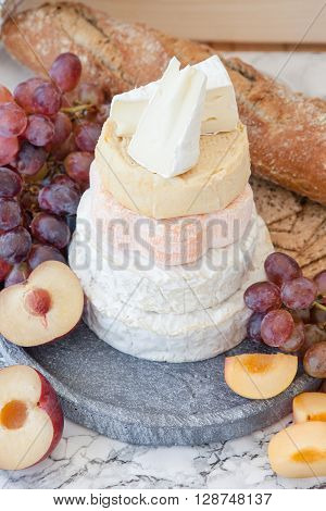 Selection of soft cheeses in a stack with fresh fruits