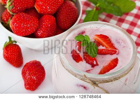 Strawberry flavored yogurt with fresh berries and min leaves over a white background