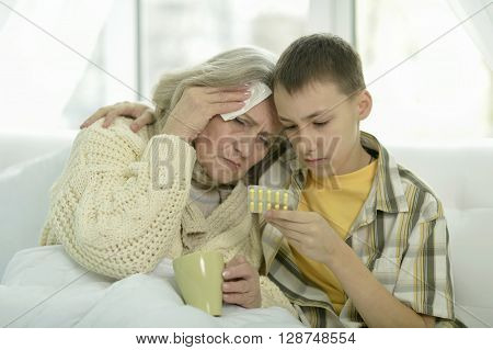 Portrait of sick  senior woman with her grandson in bed