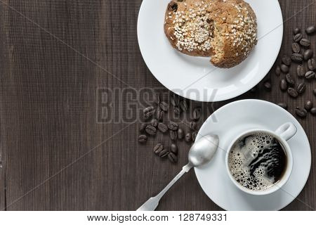 Black coffee with froth in white porcelain cup coffee beans and oatmeal cookies on a dark wooden background top view