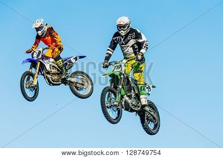 Miasskoe Russia - May 02 2016: closeup of two motorcyclists jump from a mountain on background of blue sky during Cup of Urals motocross