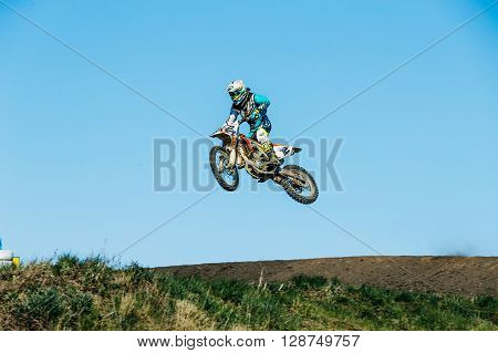 Miasskoe Russia - May 02 2016: racer motorcycle jump from mountain on a blue sky background during Cup of Urals motocross