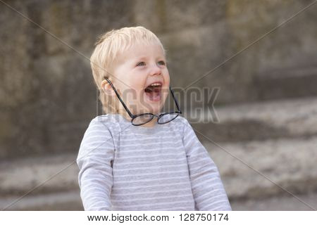 Happy child with falling down glasses outdoors