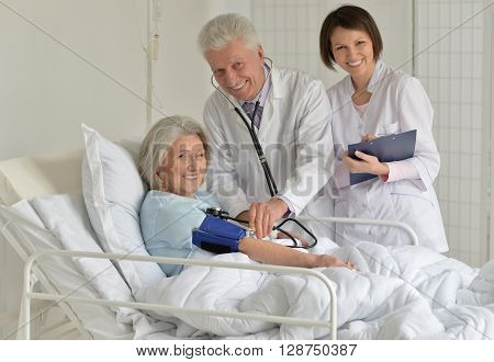 Senior woman in hospital with caring doctors