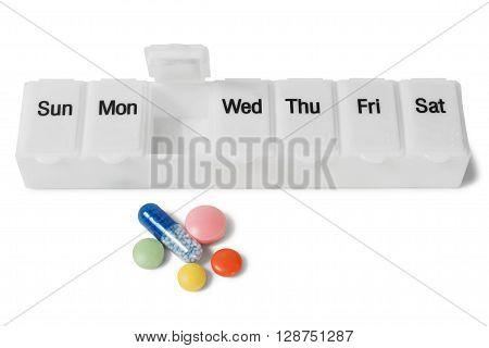 Medicine organizer and pills on white background