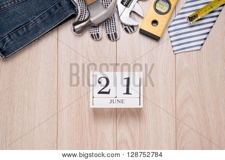 Happy father's day. Top view Greetings card of desk with laptop, tie, coffee cup, notebook, pen, calendar and smartphone on wooden backround.
