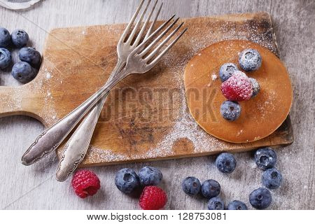 Home-made breakfast or brunch: american style pancakes served with berries and sugar powder on an old cutting board, top view