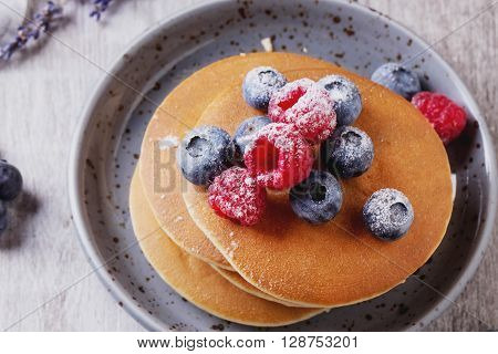 Home-made breakfast or brunch: american style pancakes served with berries and sugar powder on ceramic plate, top view