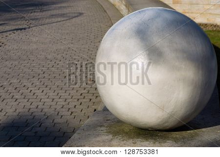 architectural abstract element in the form of the sphere closeup on an indistinct background of a sidewalk stone blocks