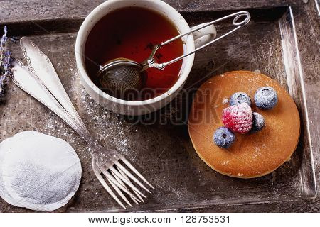 Home-made breakfast or brunch: american style pancakes served with berries and sugar powder on vintage metal tray with a cup of black tea, top view