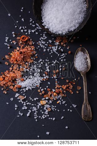 Sifting sea salt in an old black metal bowl and Himalayan rose rock salt with chili spices in a spoon over black background.