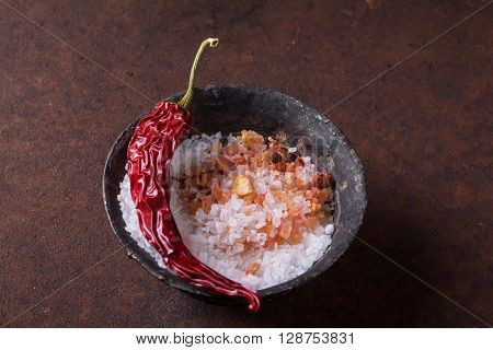 Sifting sea salt in and Himalayan rose rock salt with chili spices in an old black metal bowl over rustic metal background.