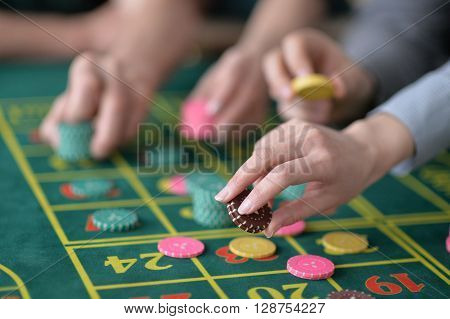 human hands playing with  casino chips close up