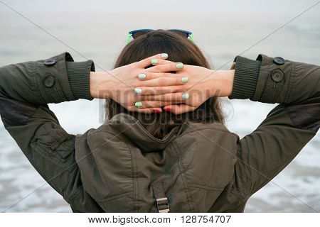 Girl In The Green Jacket With A Hood Looks On The Sea Put Her Hands On The Back Of The Head