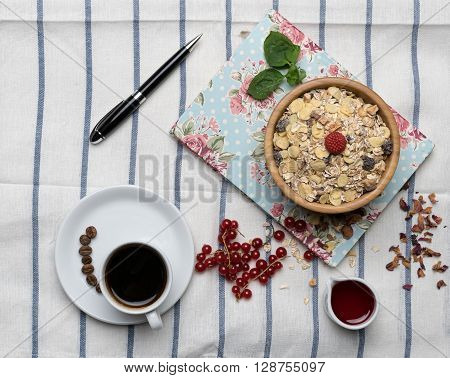 Healthy breakfast with muesli raspberry cherries and coffee on a background of white tablecloth block note and black pen