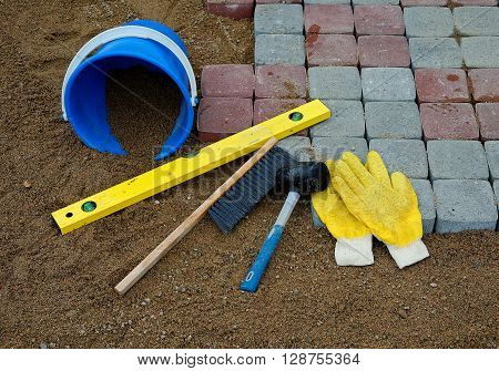 Pavement details stone bricks rubber hammer level gloves and tape measure