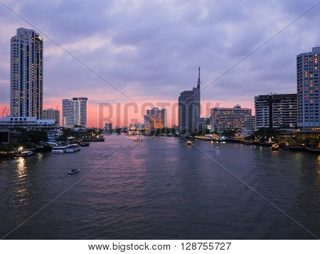 Cityscape and modern building near the river Night light at Chao Phraya River in Bangkok Thailand