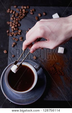 A cup of coffee on black slate board with coffee beans, sugar and tiny sugar tongs. Male hands putting sugar in the cup. Top View
