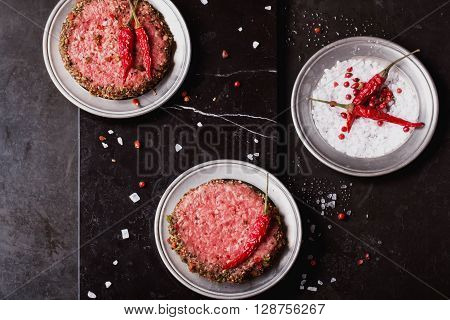 Raw Ground beef meat Burger steak cutlets with spices on dark marble background