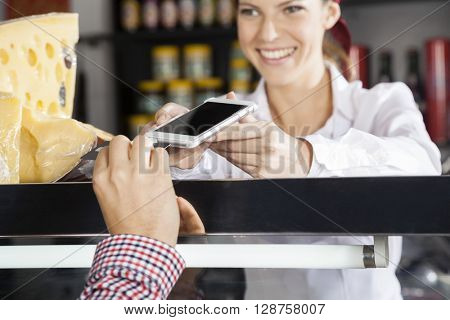 Saleswoman Accepting Payment From Customer Through Credit Card