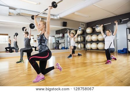 Female And Male Friends Lifting Barbells In Gym