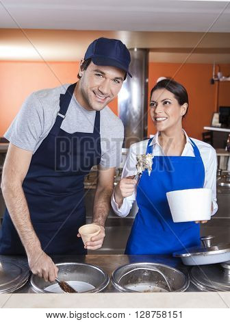 Worker Working With Coworker At Counter In Ice Cream Parlor