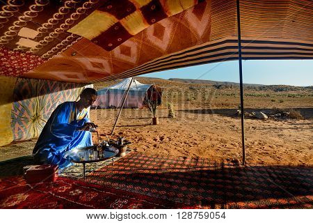 GUELMIMA, MOROCCO - OCTOBER 25, 2015:  Berber man preparing tea for guests at a camp near Guelmim in the Sahara desert , Morocco.