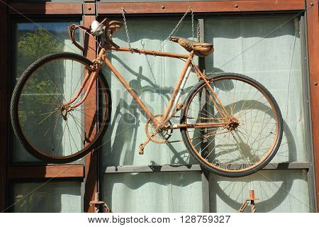 old bicycle hanging next to a glass window