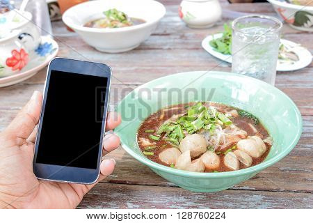 Thai noodle in green Bowl placed on wooden tableBlack display Smart phone in hand.
