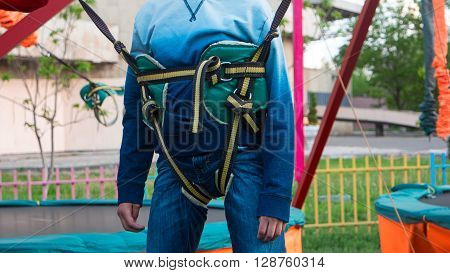 Safety belt for jumping on boy in park.