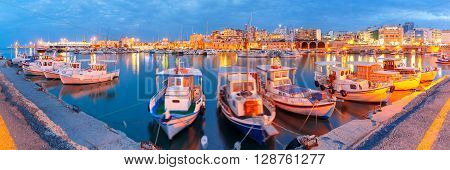 Panorama of Old harbour with fishing boats and marina during twilight blue hour, Heraklion, Crete, Greece. Boats blurred motion on the foreground.