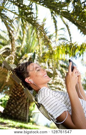 Smiling Woman Listening To Music On Hammock Outdoors