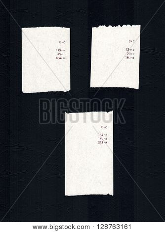 Three bills or receipts isolated over black background