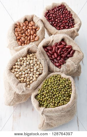 Assortment Of Beans And Lentils In Hemp Sack On Wooden Background. Green Bean, Groundnut, Soybean, R