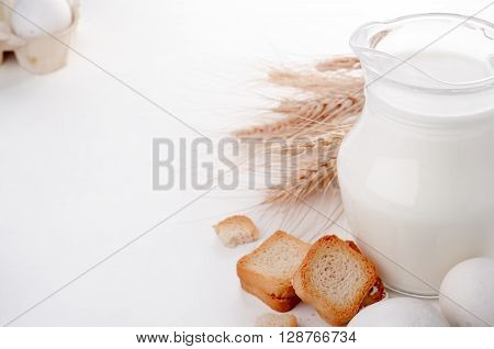 Glass Jug With Milk, Wheat Seeds And Two Eggs